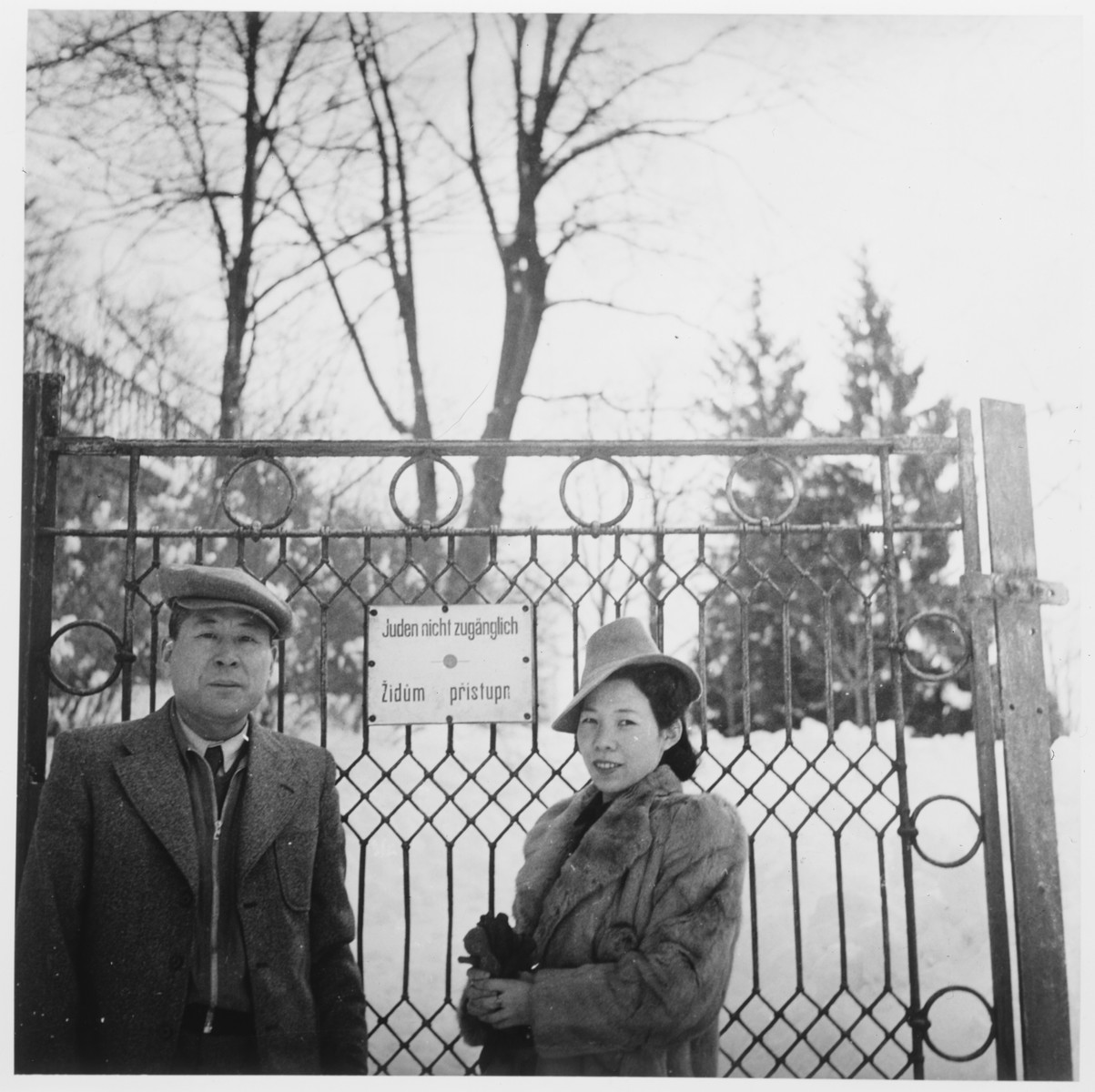 """Chiune Sugihara and his wife Yukiko pose in front of the gate to a park in Prague.  The posted sign  reads, """"Jews not allowed"""" in German. However the lower line in Czech reads """"Jews Allowed"""". Someone as covered or scratched out the no in the Czech line."""