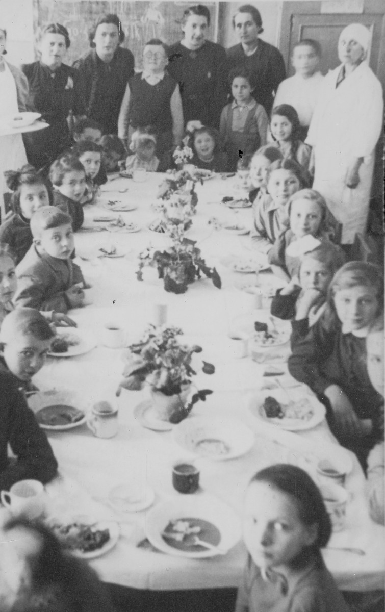 Lejb Melamdowicz celebrates the ninth birthday of his friend Masha Bernsztejin with family and schoolmates.   Seated on the right are Olenka Lazar, Rochke Stollen, Masha Bernsztejin, Dorotka Goldsztein, and Dinele Bachrach.  In the back left is Chaya Sora Kaufman.  Seated in the back are Sarah Elbaum, standing behind her is her mother, Esther Elbaum, and standing in the left corner, Mrs. Mandelman.    (Sarah Elbaum has also been idenitied as Sarenka Elboim. The child to her right is not her sister, as originally reported.)