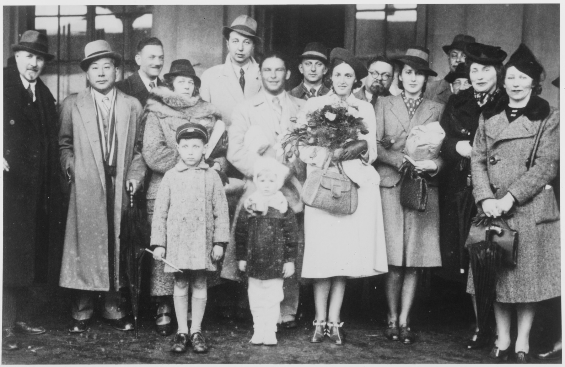 Chiune Sugihara poses with a group of people at the railroad station in Kaunas on the occasion of the departure of Polish army lieutenant Stanislaw Kaspcik and his wife, Stella Kominskaya.    Sugihara helped Kaspik, who was a well-known anti-Bolshevik, to escape from Soviet controlled Kaunas.  Kaspik and his wife are pictured in the center.