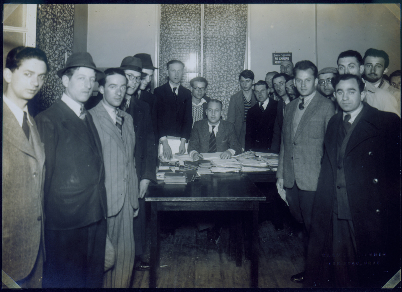 "A group of men surround a ""JEWCOM"" official as he collects travel documents."