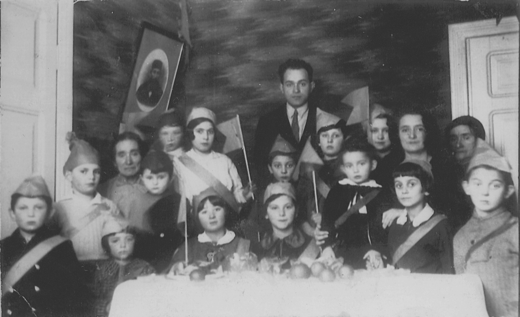 Lejb Melamdowicz's third birthday, Bialystok, 1935.   Melamed's father (center), grandmother and mother (far left and far right, respectively) join a group of children in hats and sashes around a table adorned with fruit.
