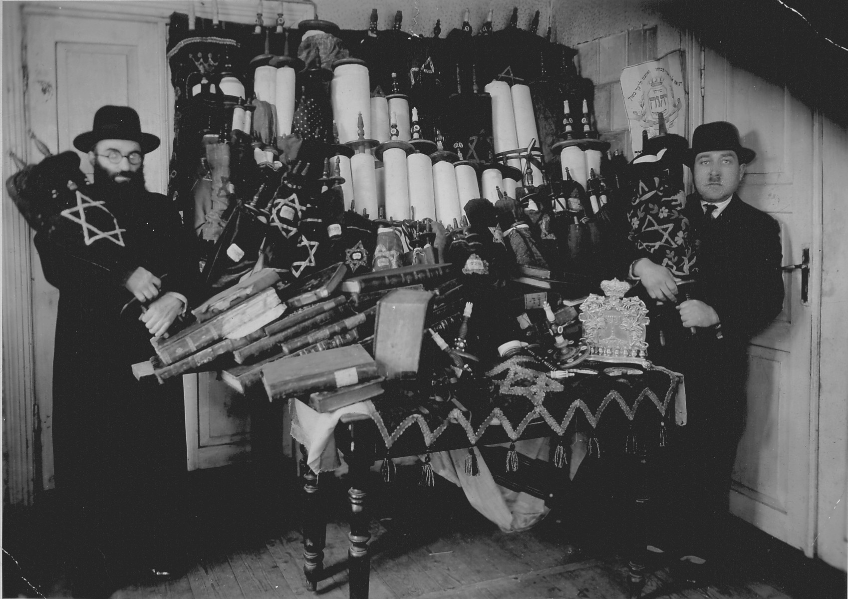 Rabbi Lifszyc (left) and another man pose in front of a cabinet full of Torah scrolls that were smuggled out of Suwalki.  Sixty scrolls and other holy items were rescued from hiding places in Suwalki, which had been occupied by Germany, and were taken to the synagogue in Kalvarija for safety.  While Lifszyc was in Vilnius, he tried to save the Torah scrolls from the Russian occupiers, but had to flee Vilnius and leave these behind.