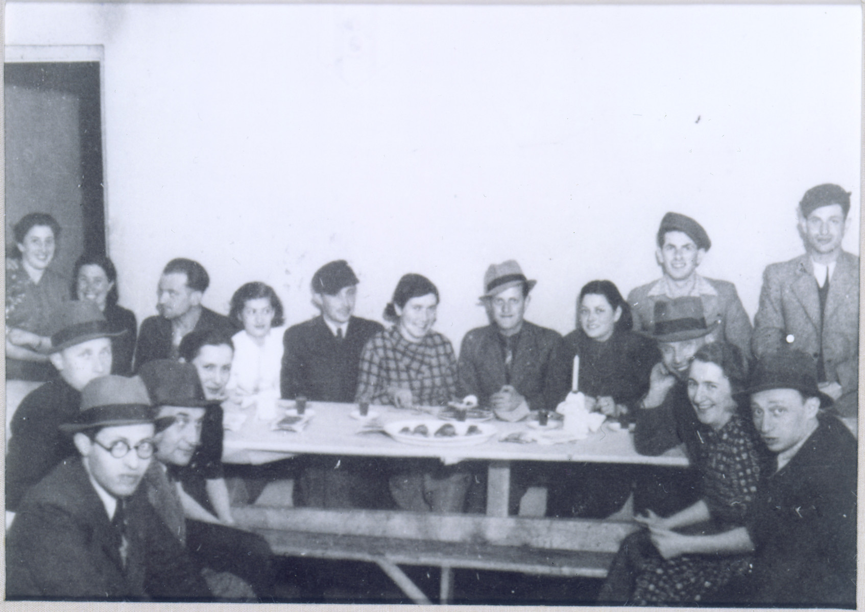 "Gathering of Polish Jewish refugees at the ""Internat"" Betar youth hostel in Vilna.    Among those pictured are Menahem Begin (at the front left); Fejga Szepsenwol (top left); and Chaya Szepsenwol (third from the right, behind the candle).  Pictured on the right are probably Batya and Israel Scheib (Eldad), future leader of the Lechi.  The Internat was one of a series of communal residences established by the American Jewish Joint Distribution Committee to help deal with the housing crisis that resulted when thousands of Polish Jewish refugees flooded into Vilna in the months following the outbreak of WWII.  The JDC grouped the refugees (who were largely unaccompanied youth) in residences according to youth movement affiliation."
