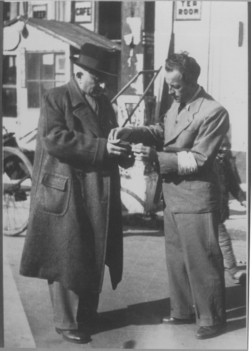 Pao Chia member with an armband examining the pass of a Jewish refugee.