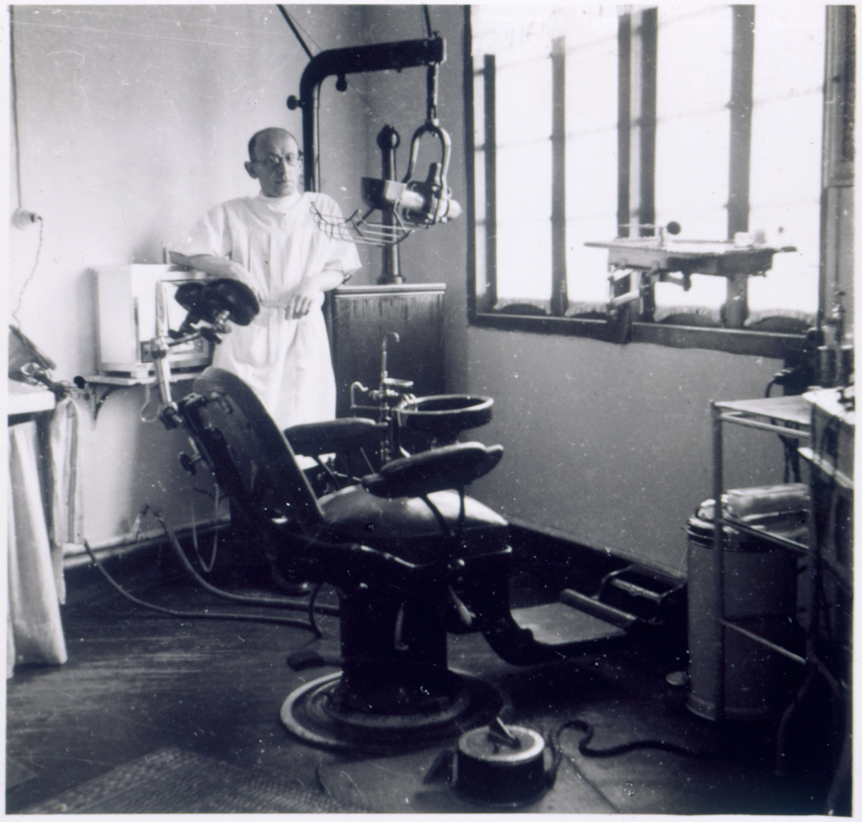 Dr. Mannes, a Jewish refugee dentist, stands in his office in Shanghai.