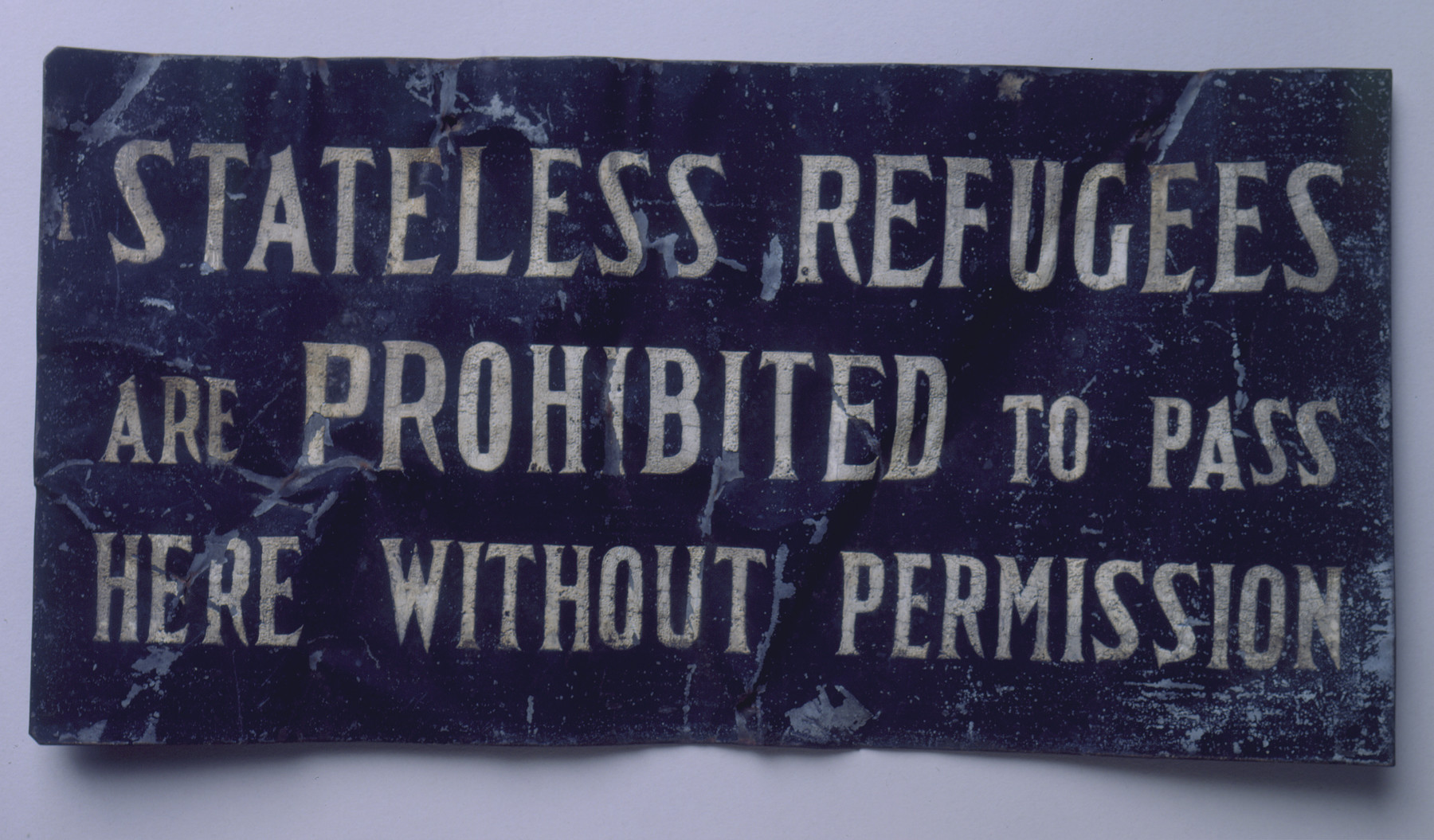 "A sign from the Shanghai ghetto, which reads: ""Stateless refugees are prohibited to pass here without permission.""  One of many signs displayed along the ghetto's boundaries, this plaque was removed by a refugee at the end of the war."