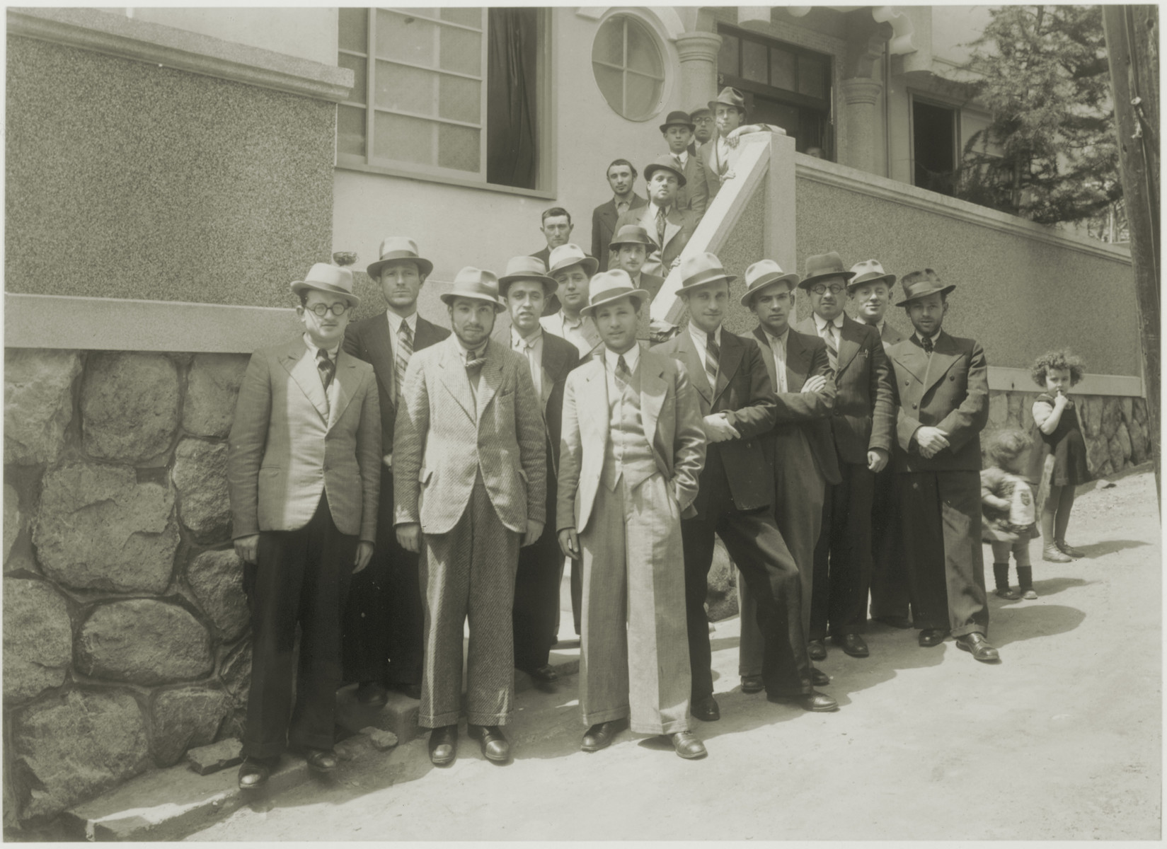 A group of students from the Mir and Lublin yeshivas gather in front of a building provided by the Jewish Committee in Kobe.   Rabbi Avraham Blumenkrantz is on the far left.  Next to him is Avraham Kravitz. Chaim Kaminsky is in the center, and Markel Greenhaus is third from the right.