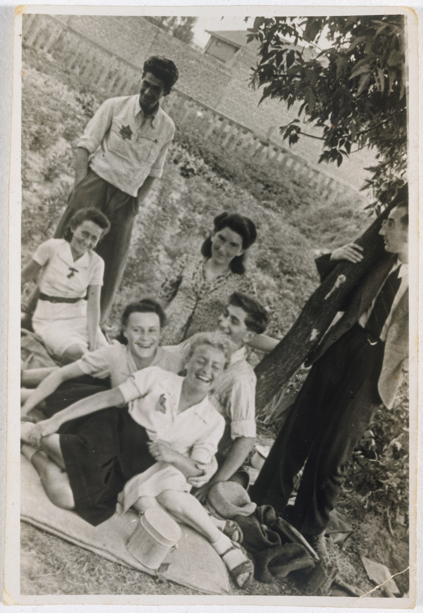 A group of young people wearing Stars of David picnic in a field outside the Lodz ghetto.  The girl in the front is Mendel Grosman's sister Rozka Grosman, the man standing on the right is Arie Princ (later Ben Menachem) and sitting in front of him is Ewa Bialer.