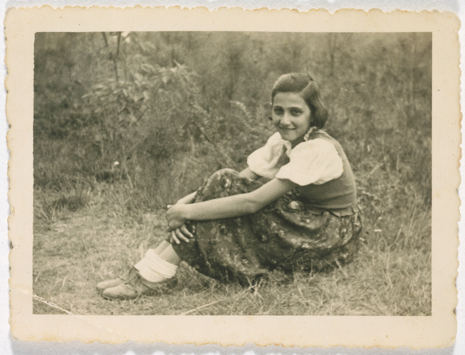 A young girl sits on a grassy field.  Pictured is Marta Rein.