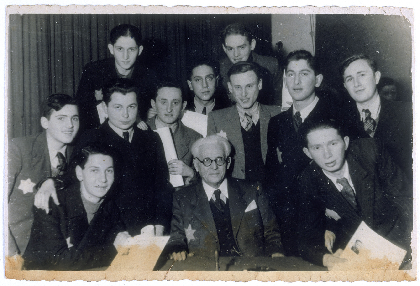 Teenagers, holding their diplomas, pose together with Mordechai Chaim Rumkowski (seated in the middle front) during their high school graduation excercise.   Itzak Rozenwasser is standing in the back row on left.  Other students are Borzykowski, Szelubski, Lubka, Margolis, Kon, Turbowicz, Hirszbein and Szwajcer.