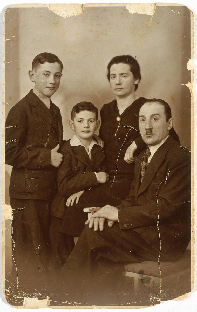 Studio portrait of a Jewish family in Lodz Poland.  Pictured are the Kozienicki family: From left: Ezra Zelig, Chaim; Chaja Sura and Szulem Kozienicki.