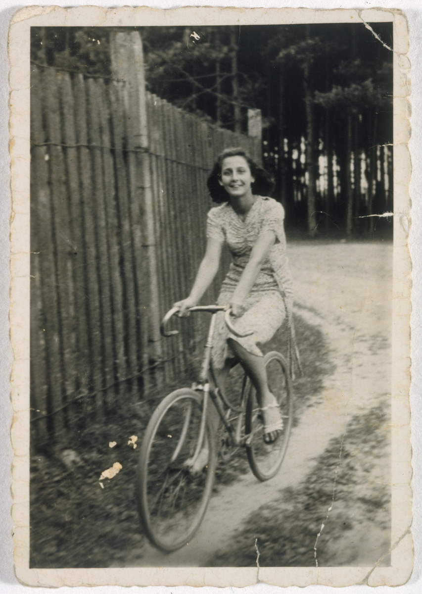 """A teenage girl rides her bicycle down a dirt path next to a wooden fence.  Pictured is Wanda Rein.  On the back she wrote to her beloved: """"Ubi Tu Caius tubi ego Caia"""" in Latin and signed: always yours Wanda."""