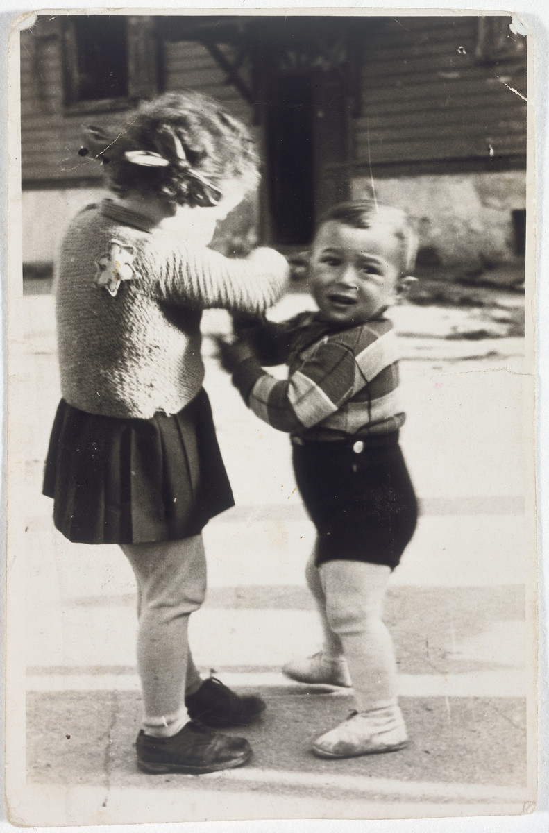 Two young children, one wearing a yellow star, play on a street in the Lodz ghetto.  Ilona Winograd is pictured on the left.