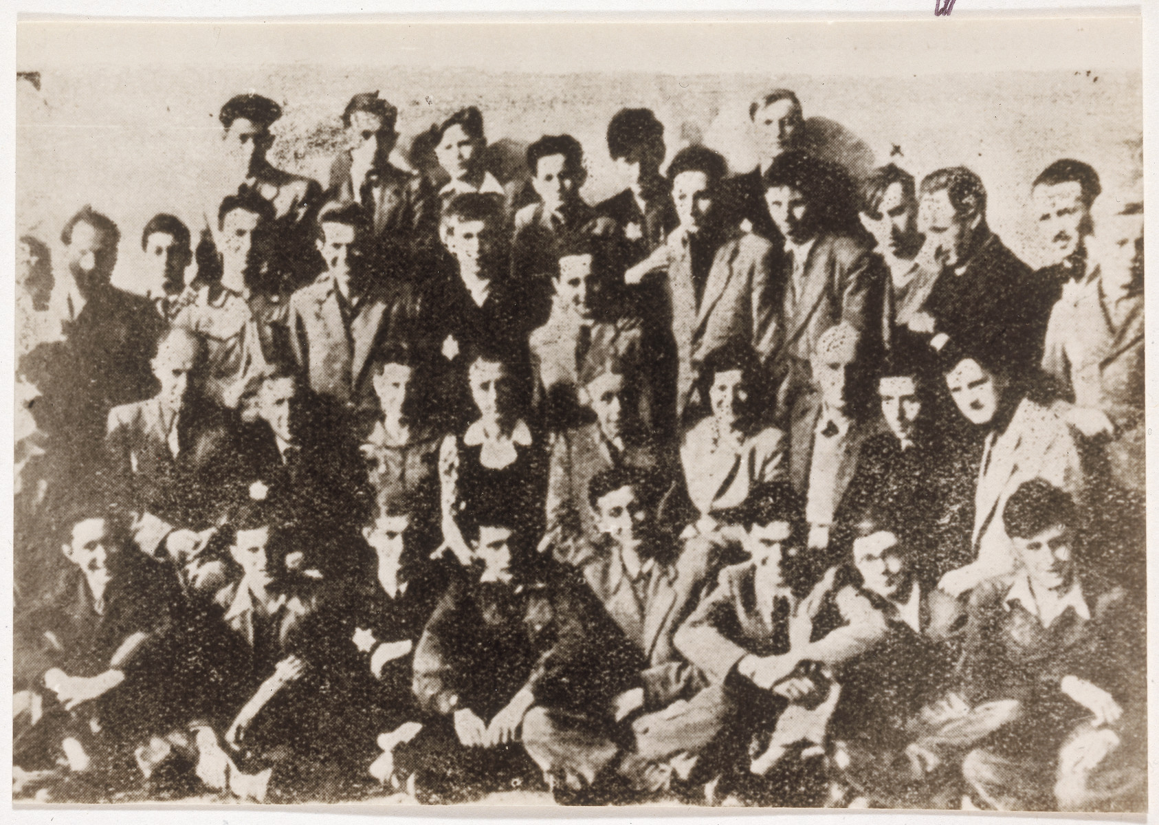 Group portrait of teenage boys [perhaps a school class] in the Lodz ghetto.   In rear right of the photograph, fourth from the right and under the x is David Sierakowiak.