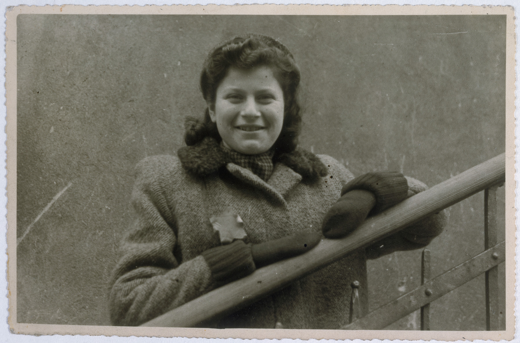 Close-up portrait of a Jewish woman wearing a yellow star and leaning on a railing in the Lodz ghetto.   Pictured is Joanna Weinberg.