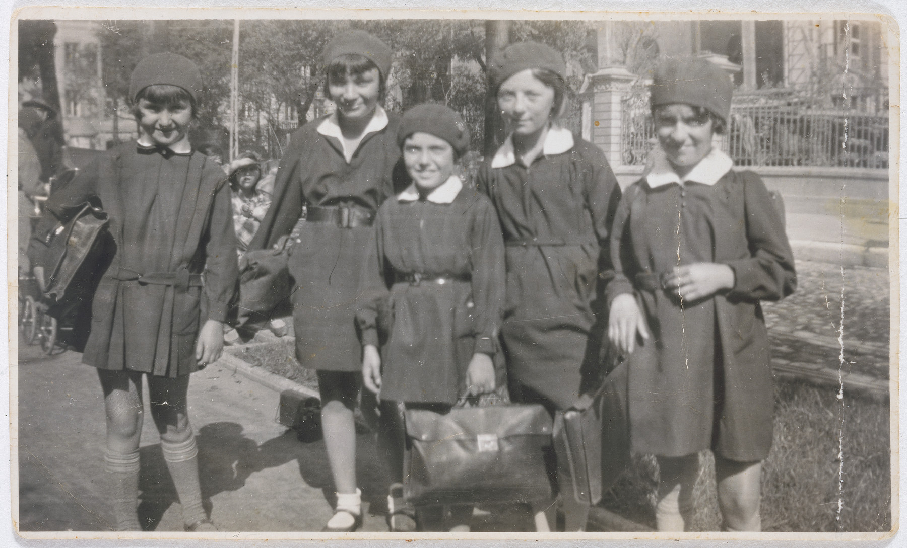 Five girls carry their book bags on their way to the Hochstein Gymnasium in Lodz.  Pictured from left to right are Mindla Reiss; Bronka Rheingold; Marysia Sheinberg; Mira Poznanska and Bela Ginzburg.      They graduated from high school in 1938.  The photograph was taken by Fania Ginzburg Rubashkin, Bela's older sister. Bronka Rheingold, Bela Ginzburg and Marysia Sheinberg were killed in the Warsaw ghetto.  Mira Poznanska was murdered together with her husband in Czestochowa.