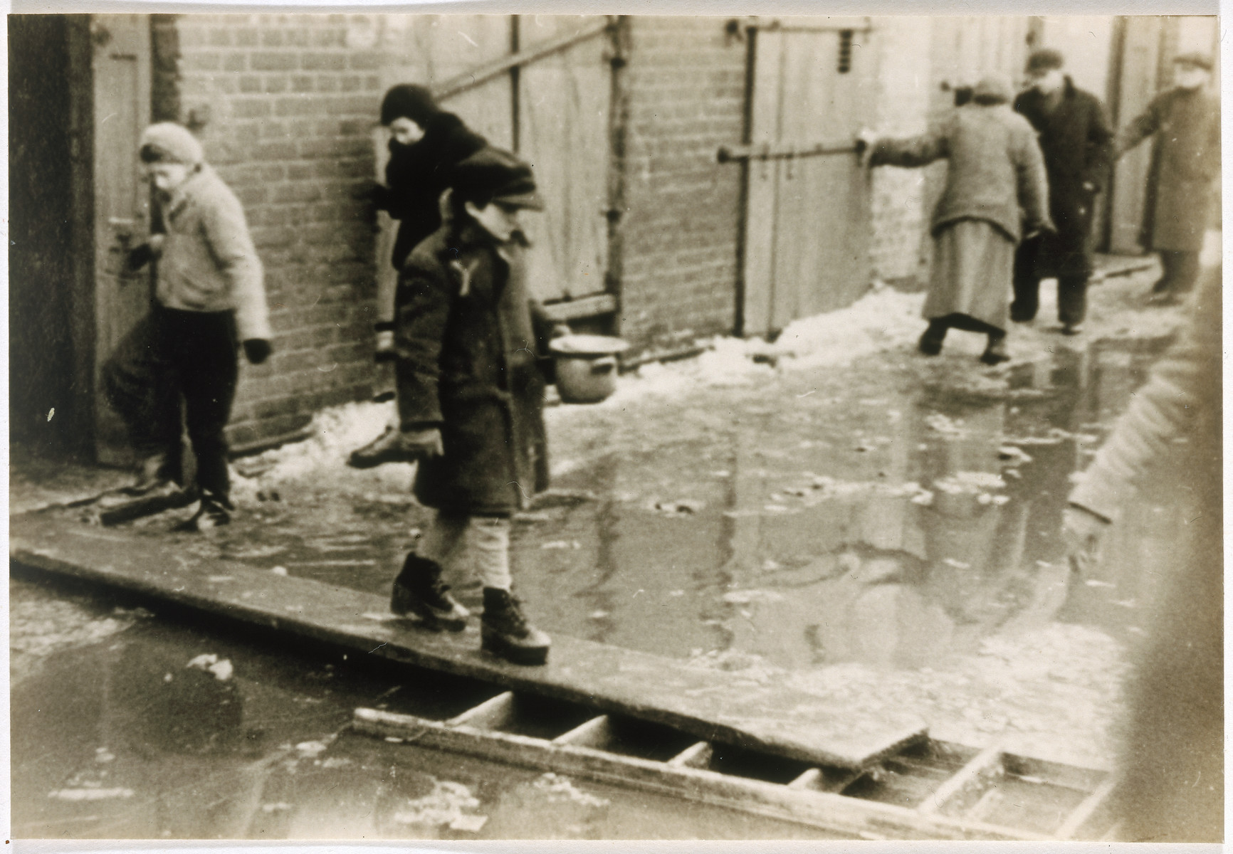A child holding a soup bowl crosses a flooded street on a plank of wood.