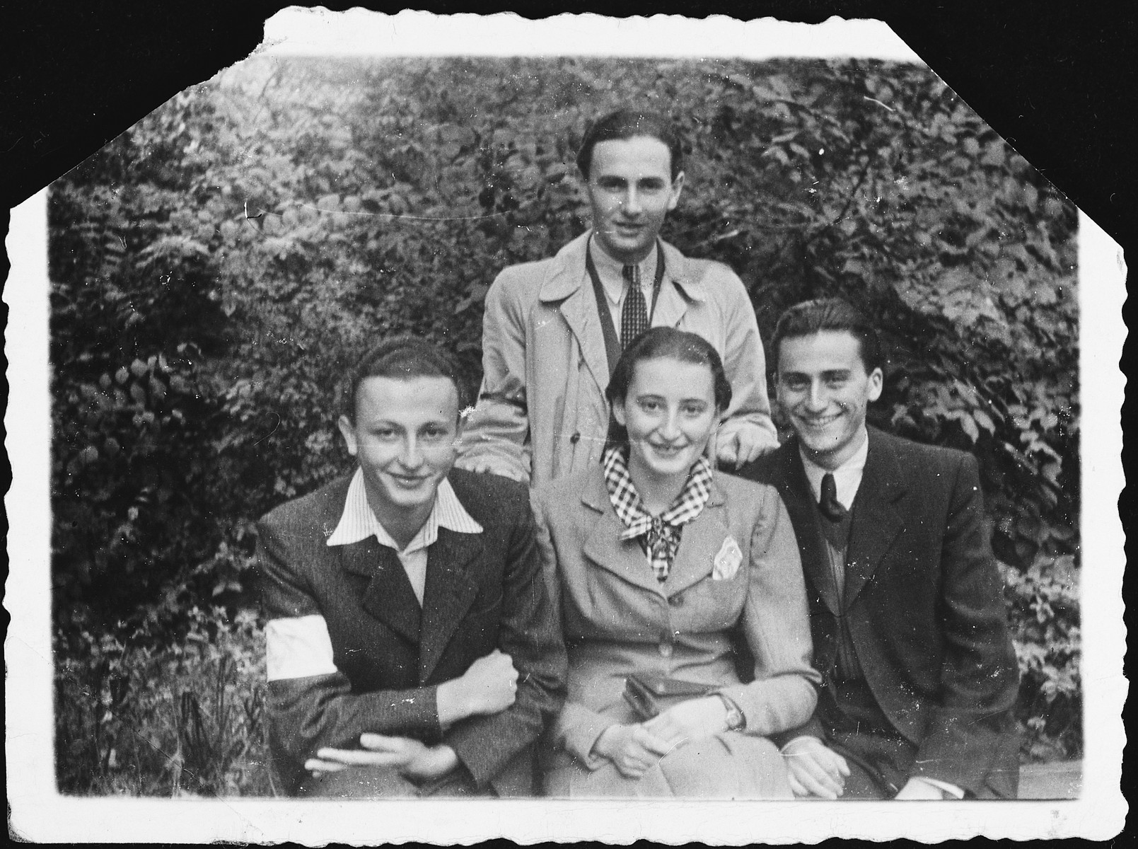 Four young people, one of whom is wearing an armband, pose together in the Krakow ghetto.  Seated from left to right are Manek Springut Werdinger, Sabina Kleiner and Garfunkel.  Standing is Josef Hilfstein.  Both Sabina Kleiner and Garfunkel perished in the Holocaust.