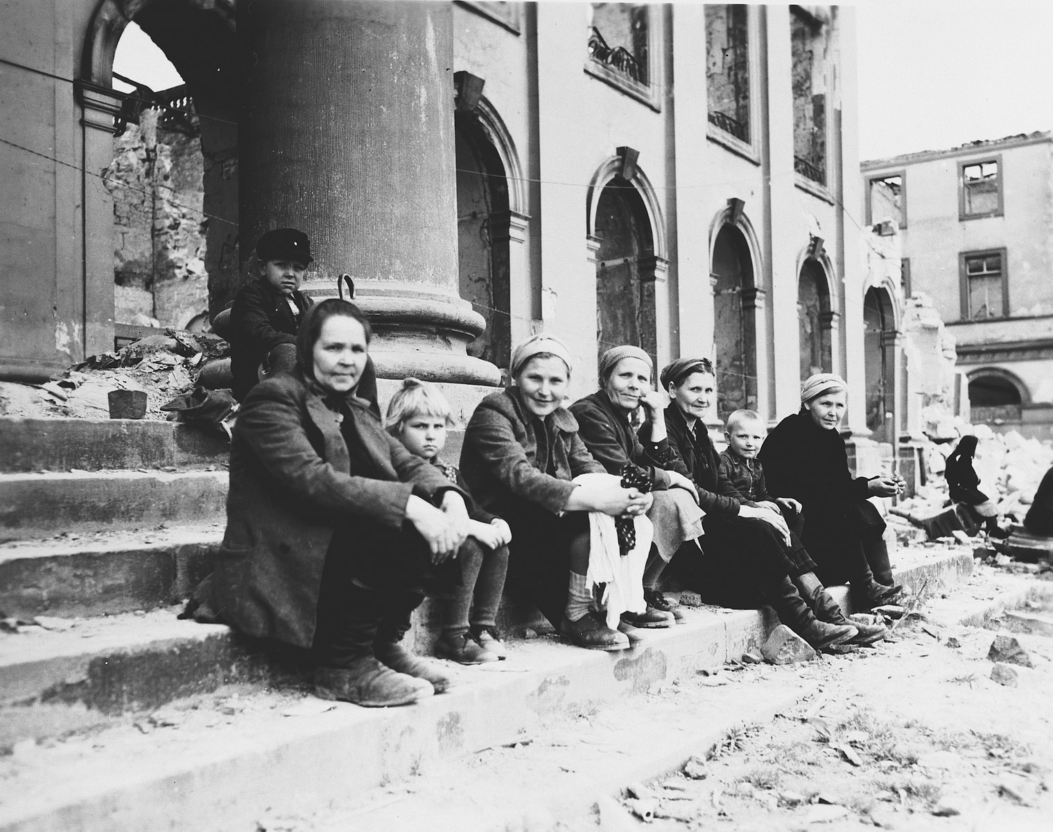 German civilian women and children sit on the steps of a largely destroyed, bomb-damaged building.