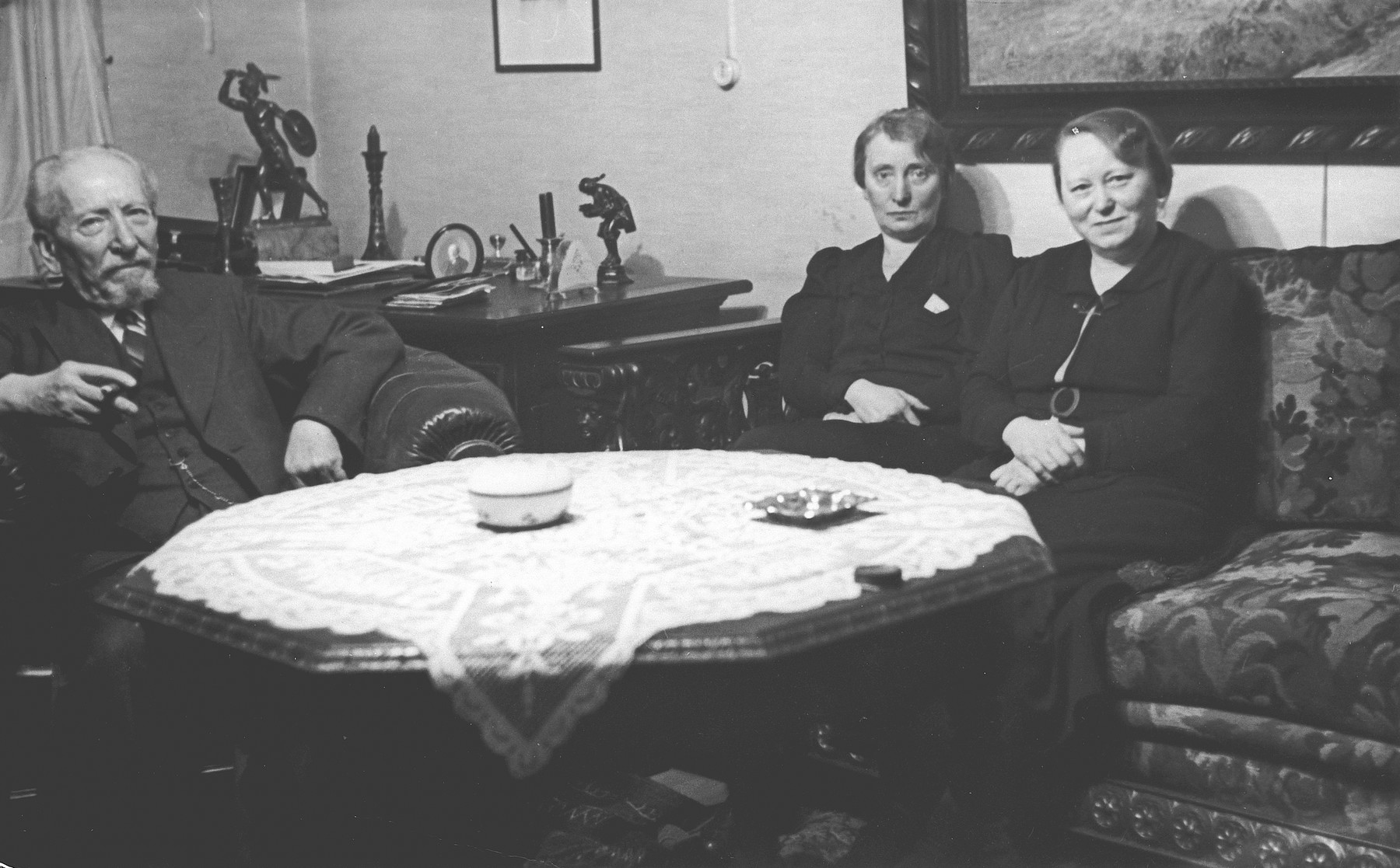 A German-Jewish family sits around a table in their home in Kassel.    From left to right are Heinrich Bluth and his daughters Rosa and Regina.