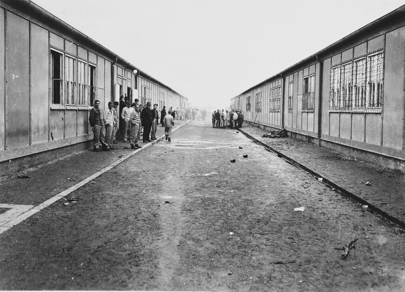 Survivors congregate on a road of the Dachau concentration camp flanked by barracks on either side.