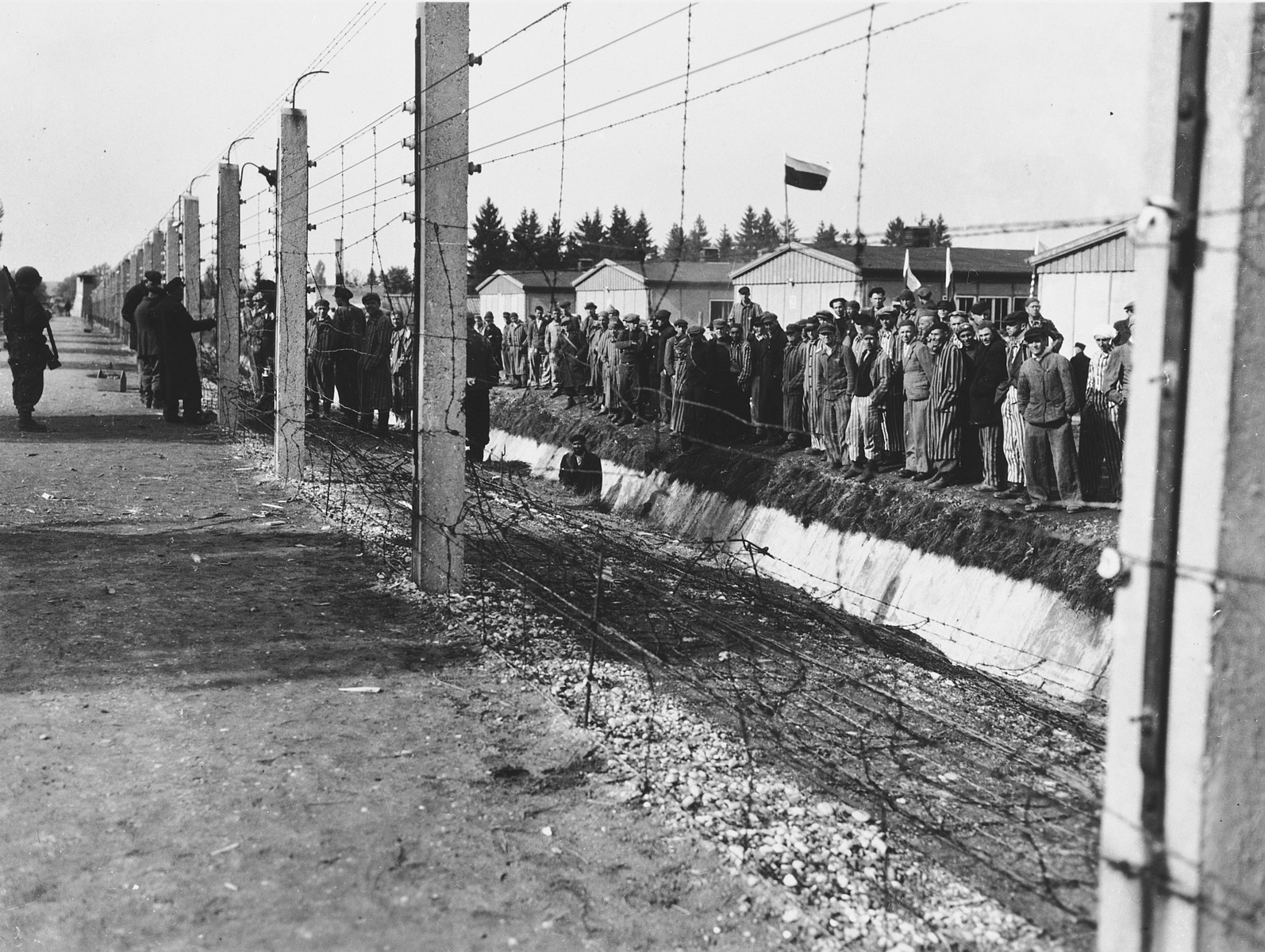 Survivors congregate next to the barbed wire fence surrounding the Dachau concentration camp.
