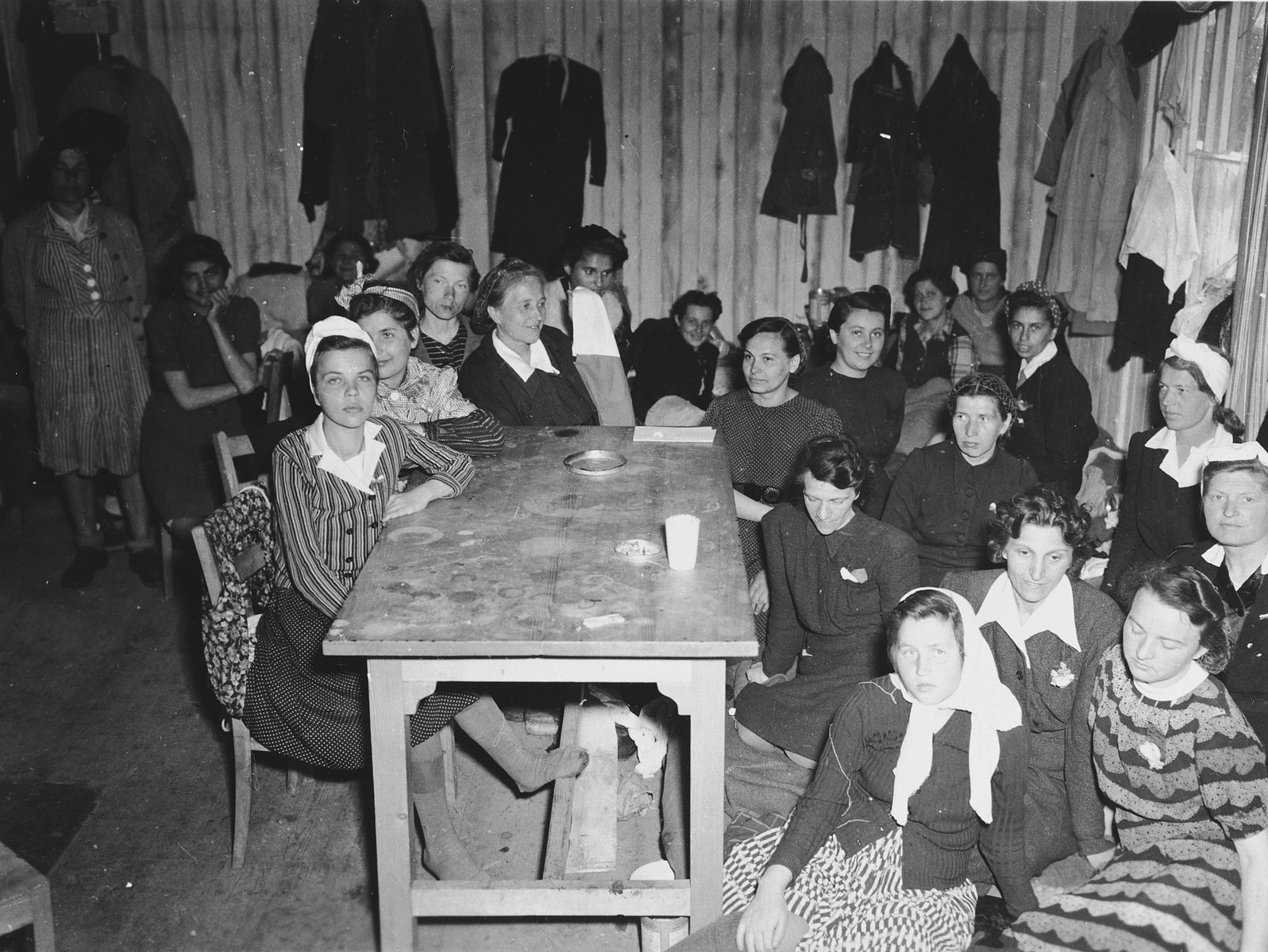 Female survivors gather by a table in a barrack of the Dachau concentration camp.