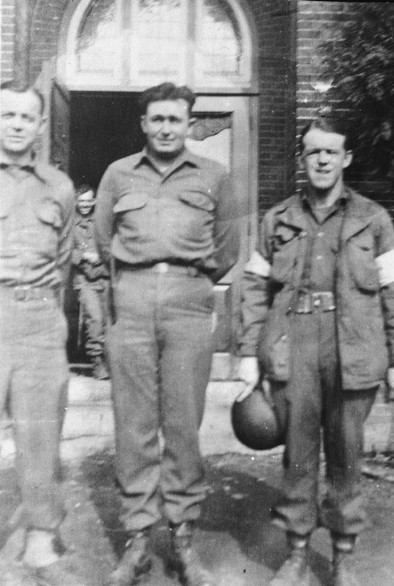Portrait of three American soldiers standing in front of a building.   Pictured on the right is Spec. William Duff.