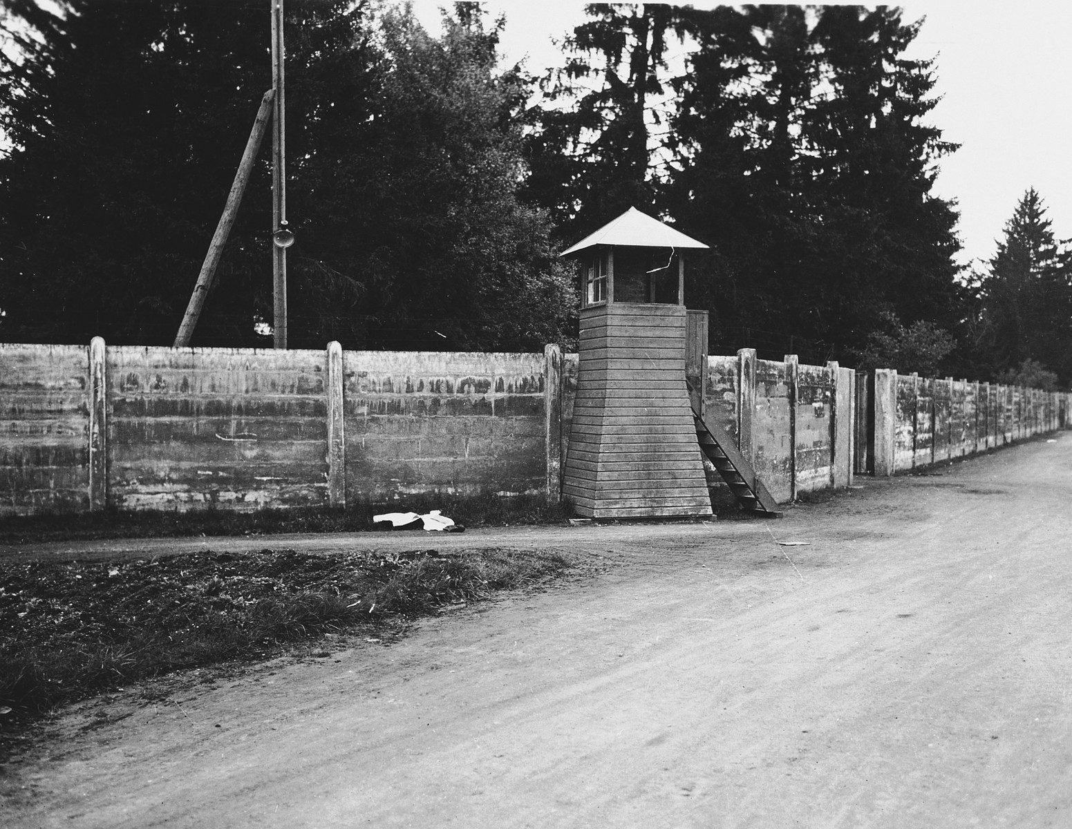 View of a wall and guard tower in the Dachau concentration camp.