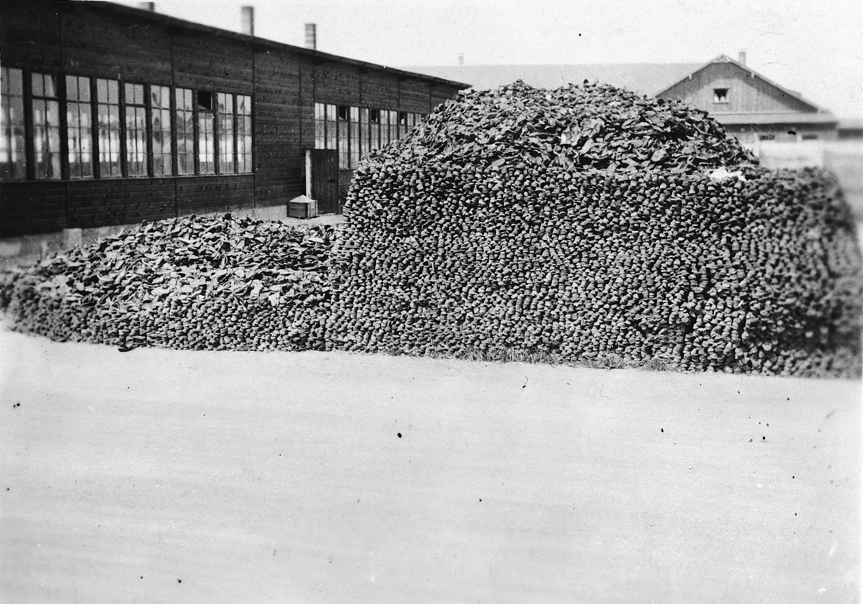 View of a large pile of victims' shoes piled up outside barracks in the Dachau concentration camp.