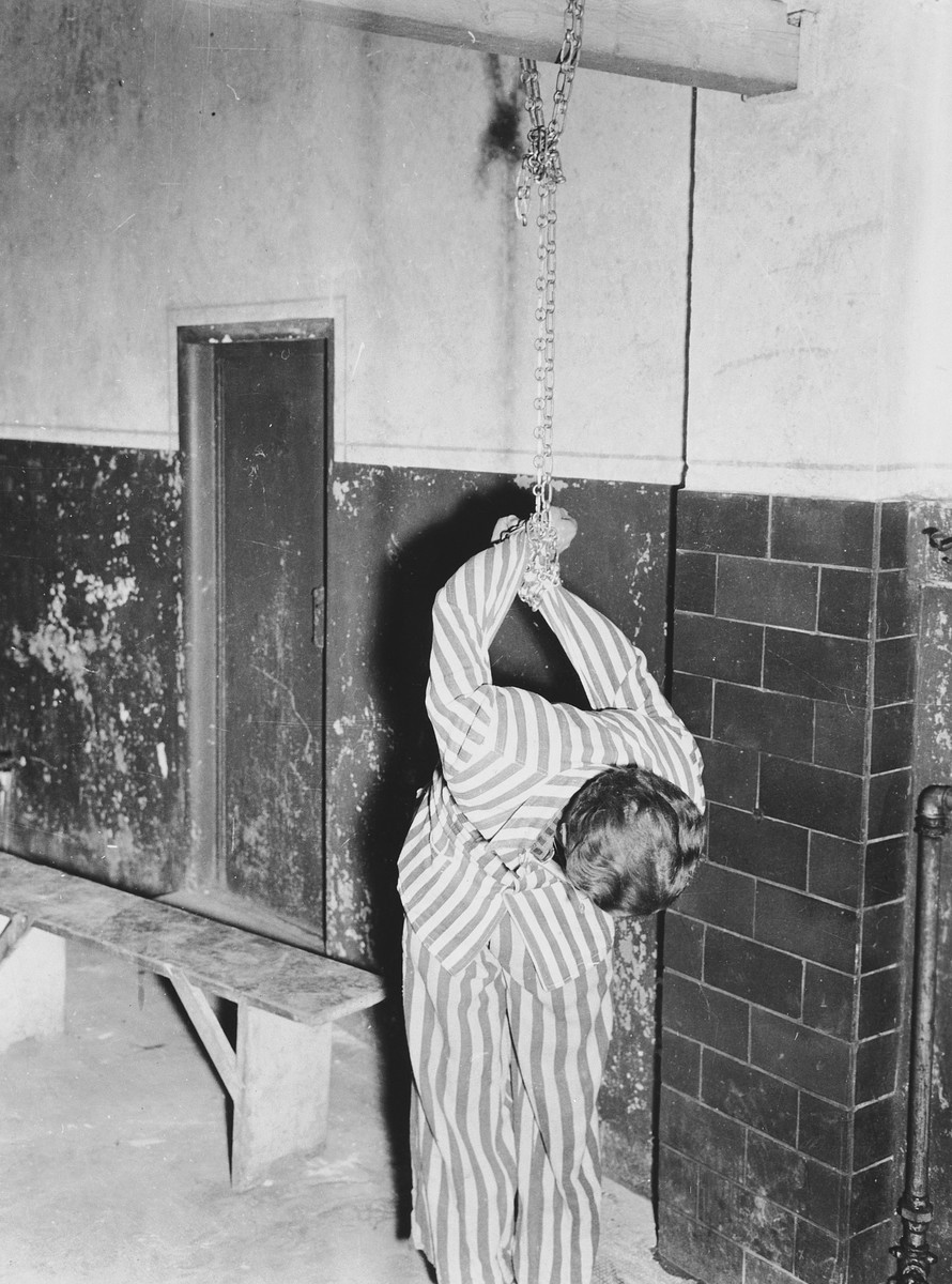 A prisoner reenacts a torture pose in the prison of the Dachau concentration camp.