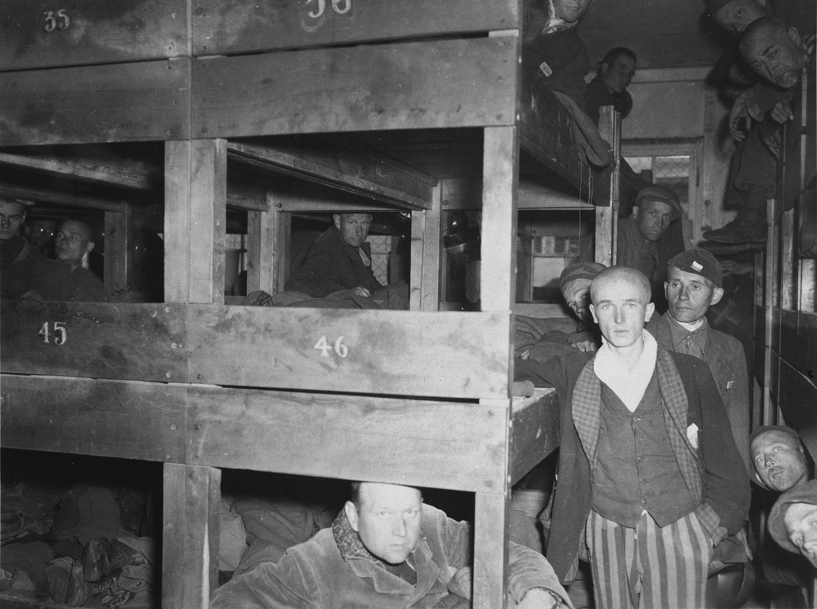 Survivors pose in and alongside their bunks in a barrack of the Dachau concentration camp.