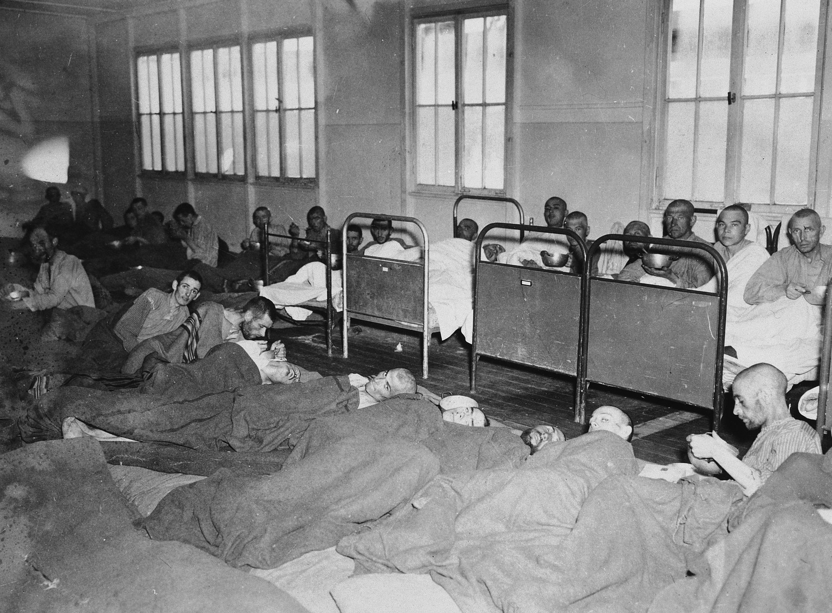Infirmed survivors lie on cots and on the floor in the infirmary of the Dachau concentration camp.