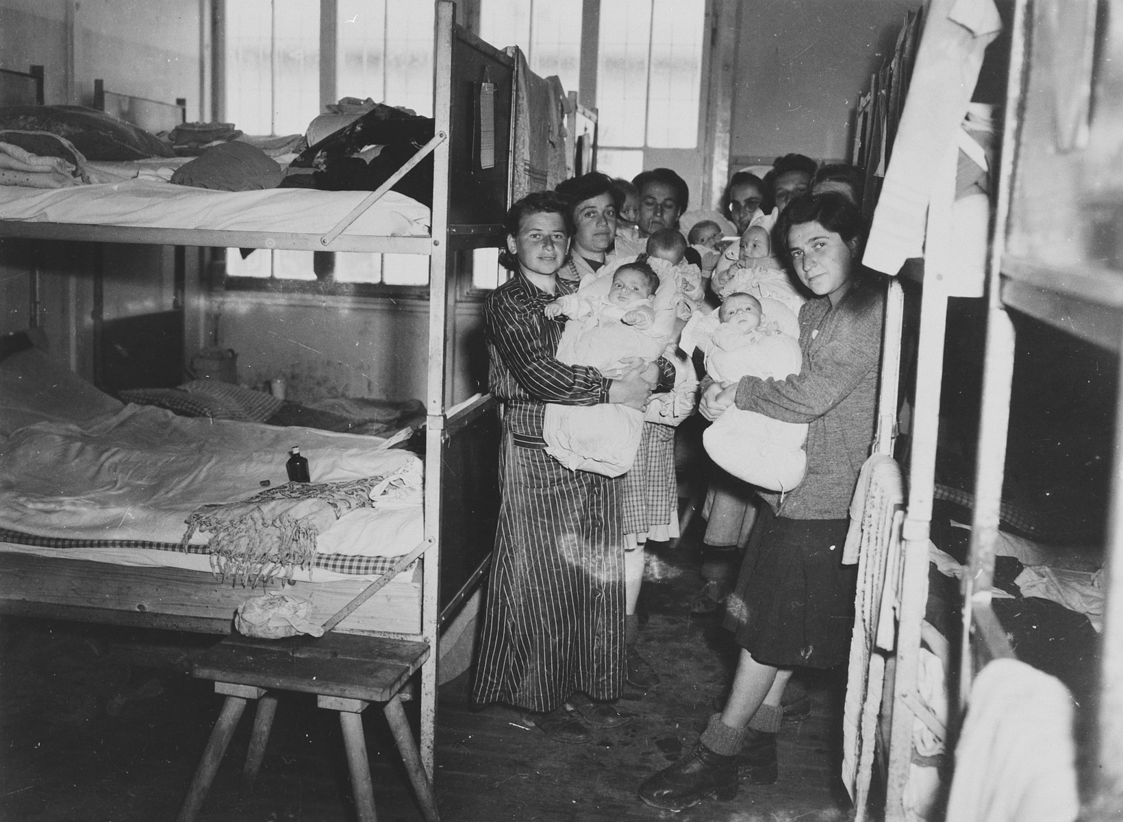 Group portrait of Hungarian Jewish mothers and their infants in a Dachau sub-camp in Germany.     Pictured left to right are Eva Schwartz with her daughter Maria; Dora Loewy and her daughter Szuszi; Boeszi Legmann with her son Gyuri; Suri Hirsch with her son Yossi; Miriam Schwarcz Rosenthal with her son Laci (Leslie); Magda Fenyvesi with her son Judit, and Ibolya Kovacs with her daughter Agnes.