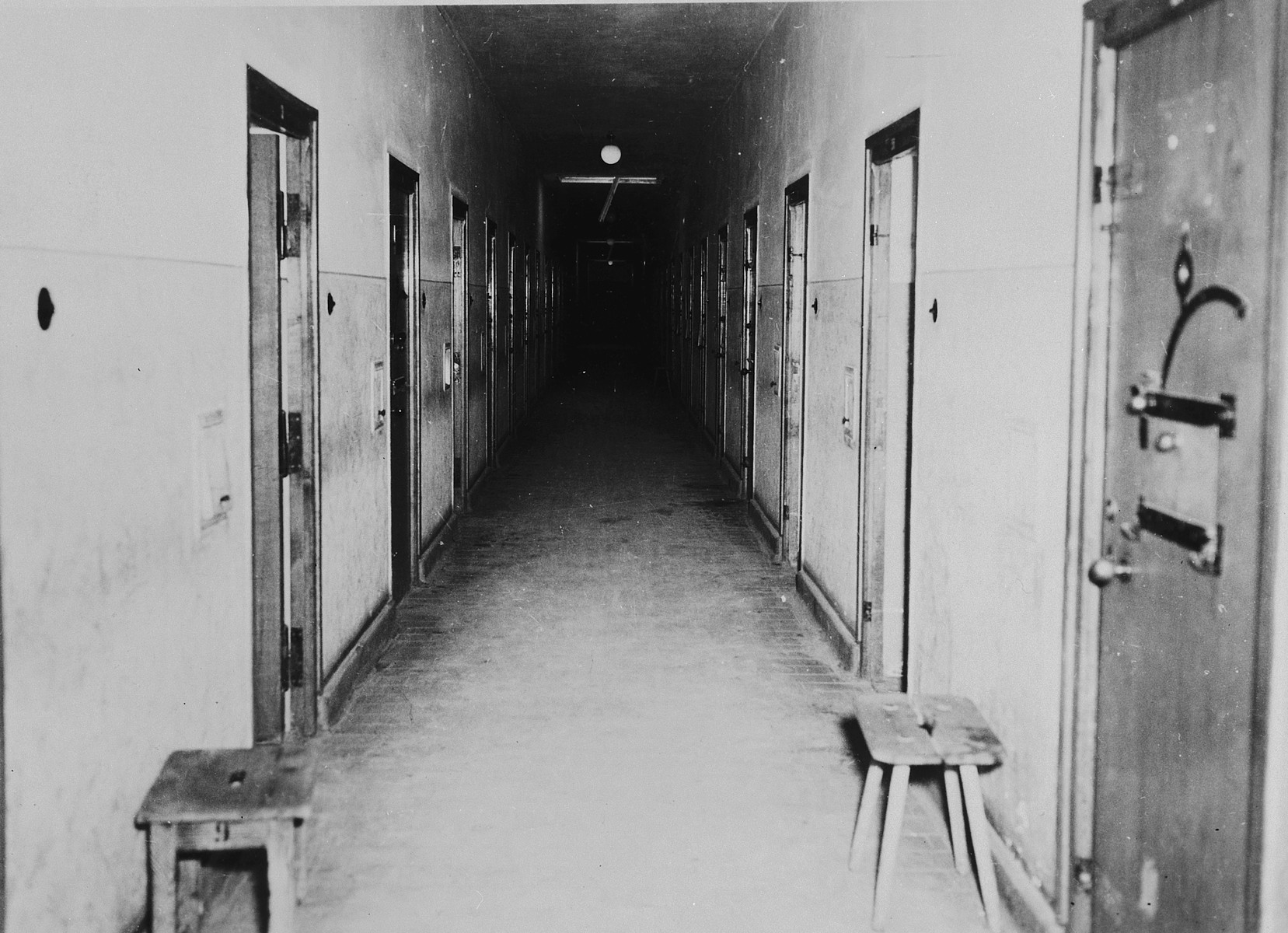 Interior view of the corridor of the prison in the Dachau concentration camp; individual cells can be seen on either side.