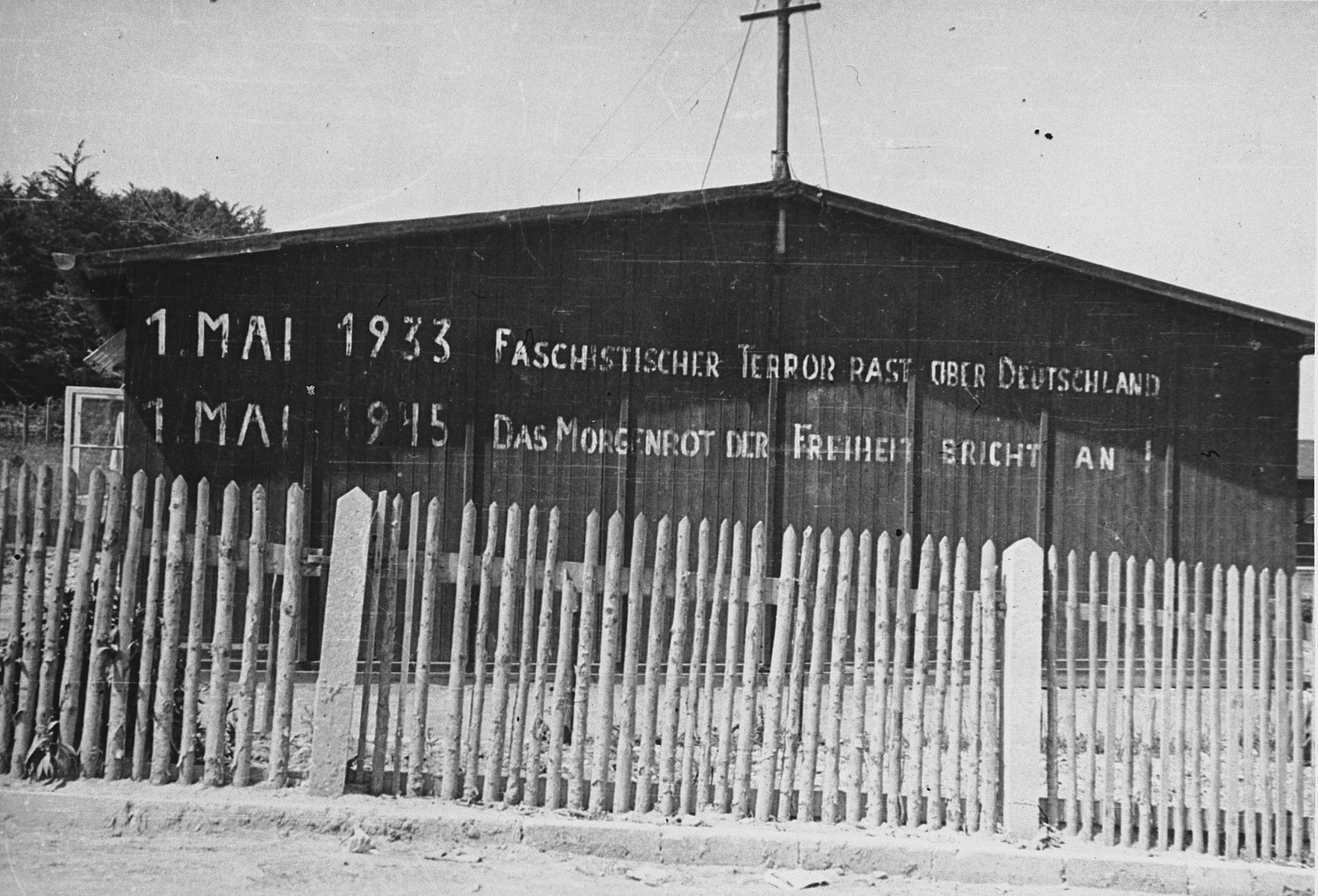 "View of an inscription printed in large block letters on the wall of a barrack in the Buchenwald concentration camp.  The inscription on the building reads, ""1 May, 1933  Fascist terror reigns over Germany.  1 May, 1945 Sunrise brings the dawn of freedom.""  The original photo caption reads, ""Shows where people have been there since 1933.  Buchenwald was in full swing about 1935.  Thousands died daily from typhus, dysentery, and T.B.  Most of them died in the crematory or the lime pit."""
