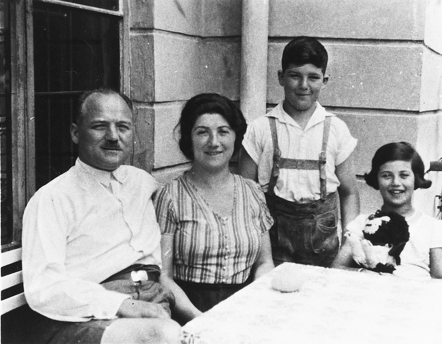 Portrait of an Austrian-Jewish family sitting around a table on a porch.  Pictured from left to right are Julius, Olga, Susi, Herbert and Susi Popper.