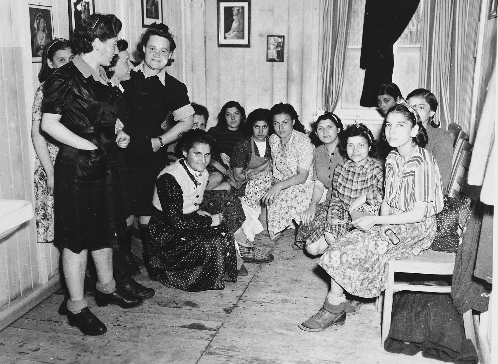 A large group of women gather in a room with curtains after the liberation of the Dachau concentration camp.