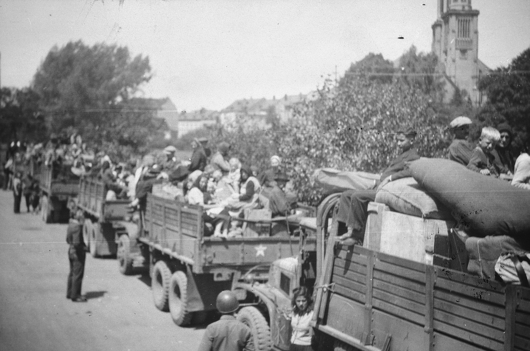 "French forced laborers crowd onto repatriation convoy trucks so that they can eventually return to France.  The original photo caption reads, ""Here are French people who were slaves in Germany.  Taking them to a French camp where all French in Germany are being held.  I was along as an aid-man for the truck drivers.  Was quite a long trip."""