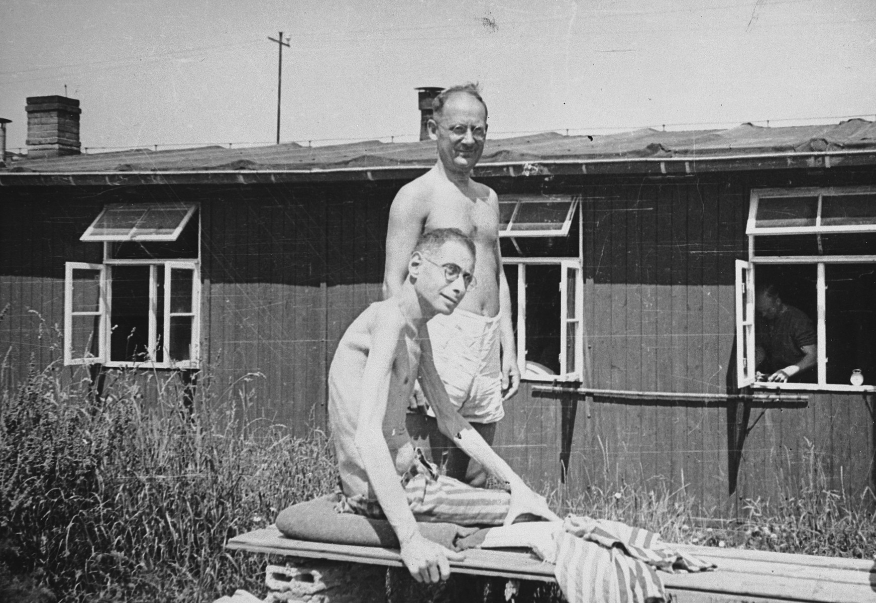 """Two emaciated survivors of the Buchenwald concentration camp pose outside the hospital barracks.  The original caption reads: """"Two prisoners at Buchenwald concentration camp: Both of these men weigh 80 pounds.  At one time they were normal human beings. Both are Poles."""""""