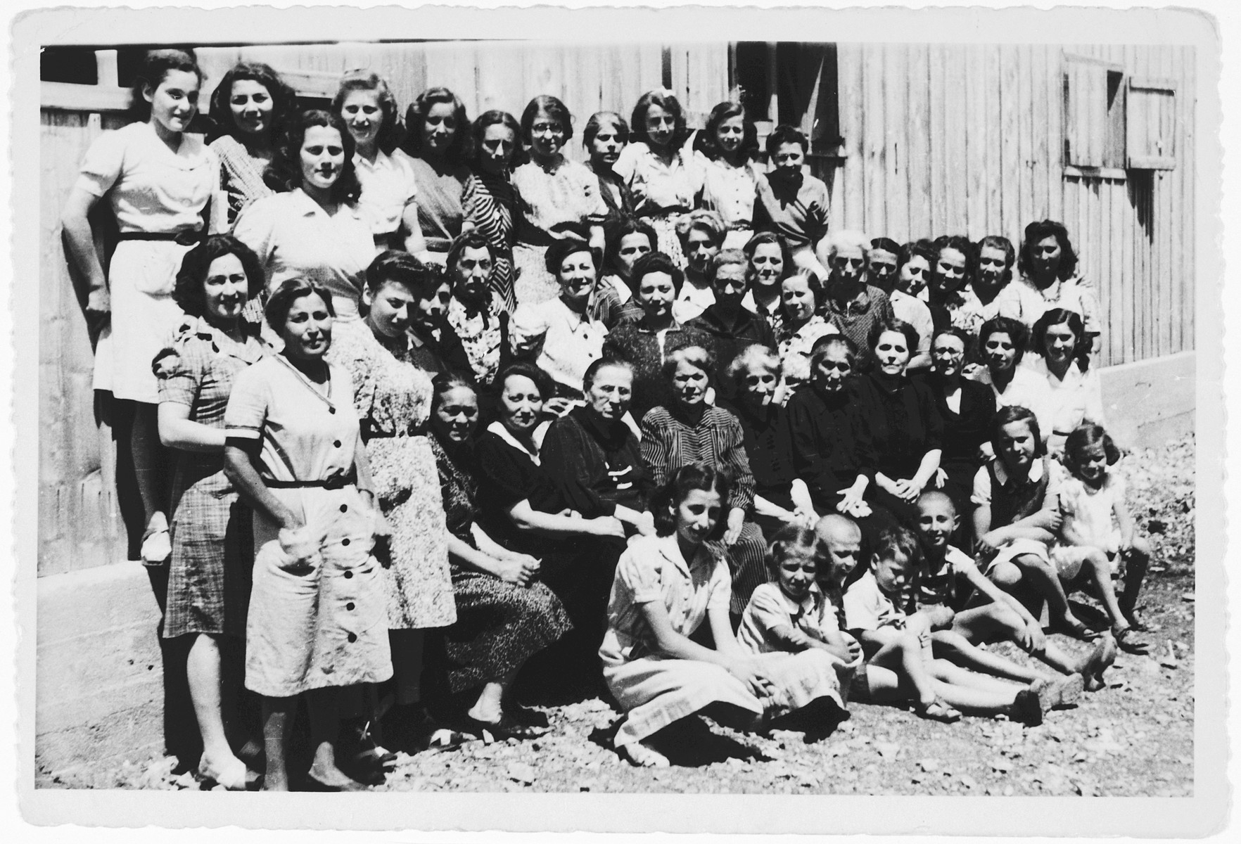 Group portrait of female and child prisoners standing and sitting outside a barrack in the Kraljevica concentration camp.  Among those pictured are Nada and Lea Gostl, school friends of the donor. Also pictured are Mira and Zora Mahler and their mother, Luisa Mahler.