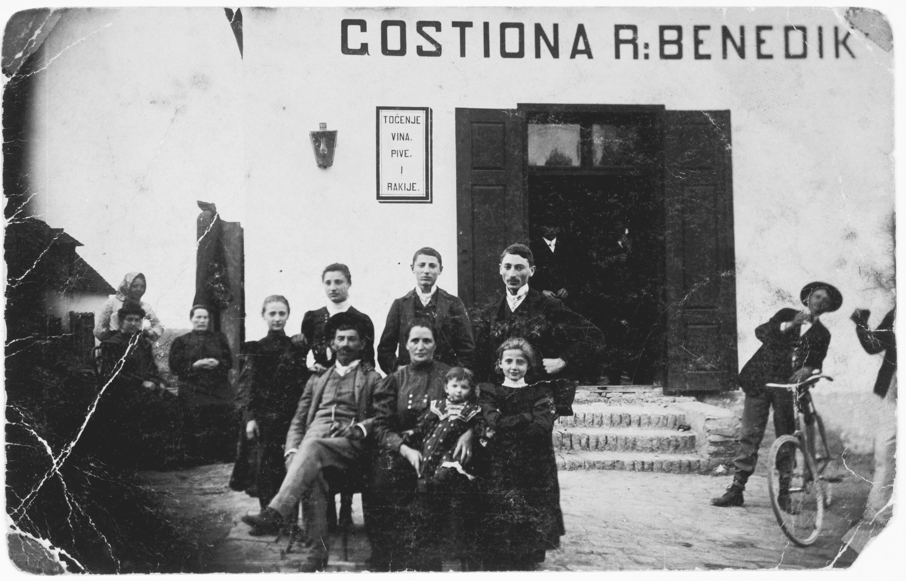 A Jewish family poses outside their inn in a small town in Croatia.  Pictured are the Benedik family.  Zora is sitting on the lap of her mother, Rosa Benedik.  Standing to her right is her sister Victoria.  In the back row are her siblings Irena, Giza, Ziga and Joseph.