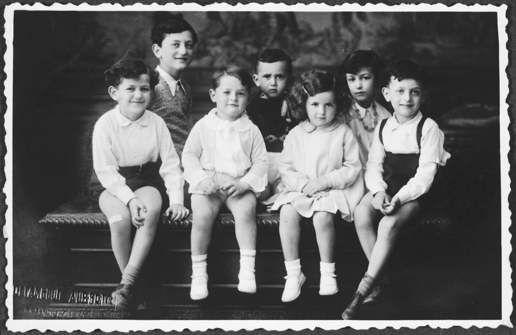 Studio portrait of seven Jewish cousins taken during the Passover holiday.   Pictured are the first cousins of Sergio Minerbi:  lower row from left: Gian Paolo (son of Ivo), Sergio (son of Arturo), Silvana (daughter of Ivo), and Giorgio-Lot (son of Leo); second row behind from left: Ruggero (son of Leo died in Kibbutz Ruhama); Enrico (son of Ivo, died at 3) and Luisa (daughter of Leo).