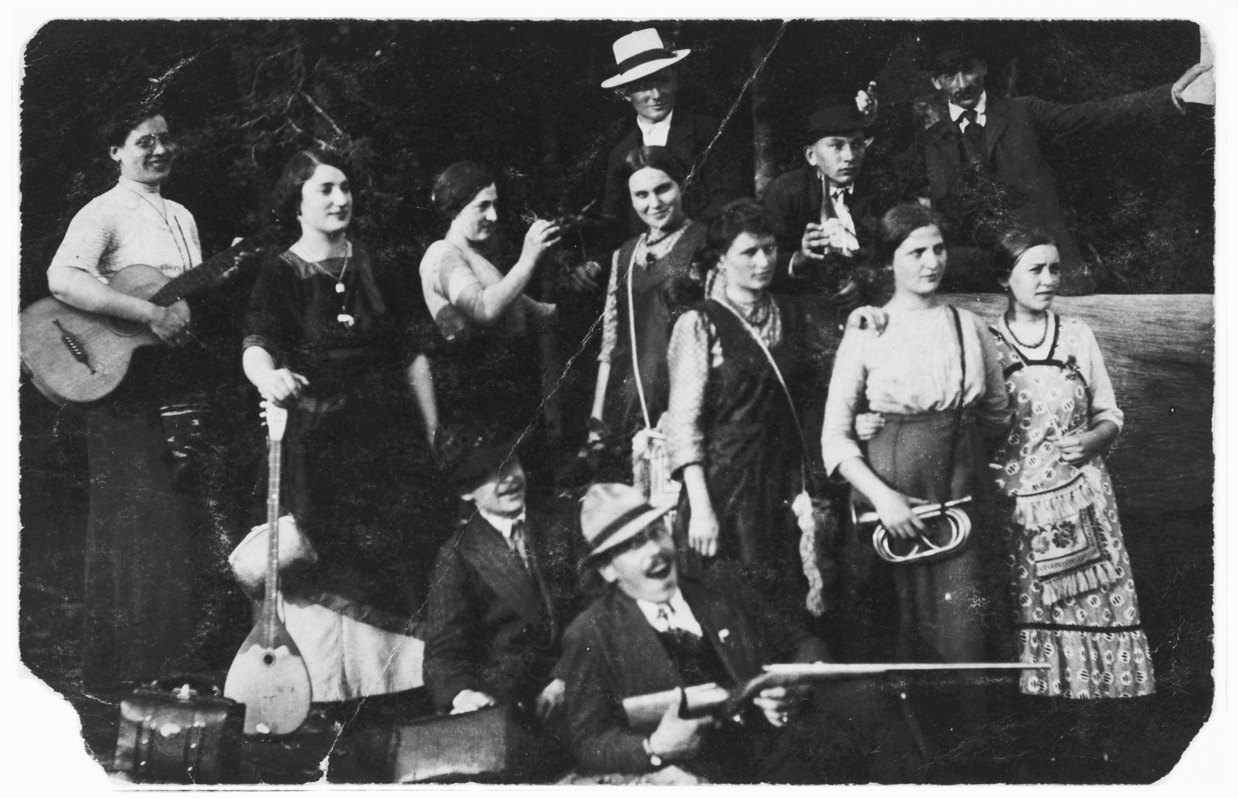 A group of Jewish young men and women from Croatia pose for a group photograph with their musical instruments.  Among those pictured are three sisters: Gizela Benedik (second from the left), Irena Benedik (third from the left) and Victoria Benedik (second from the right).