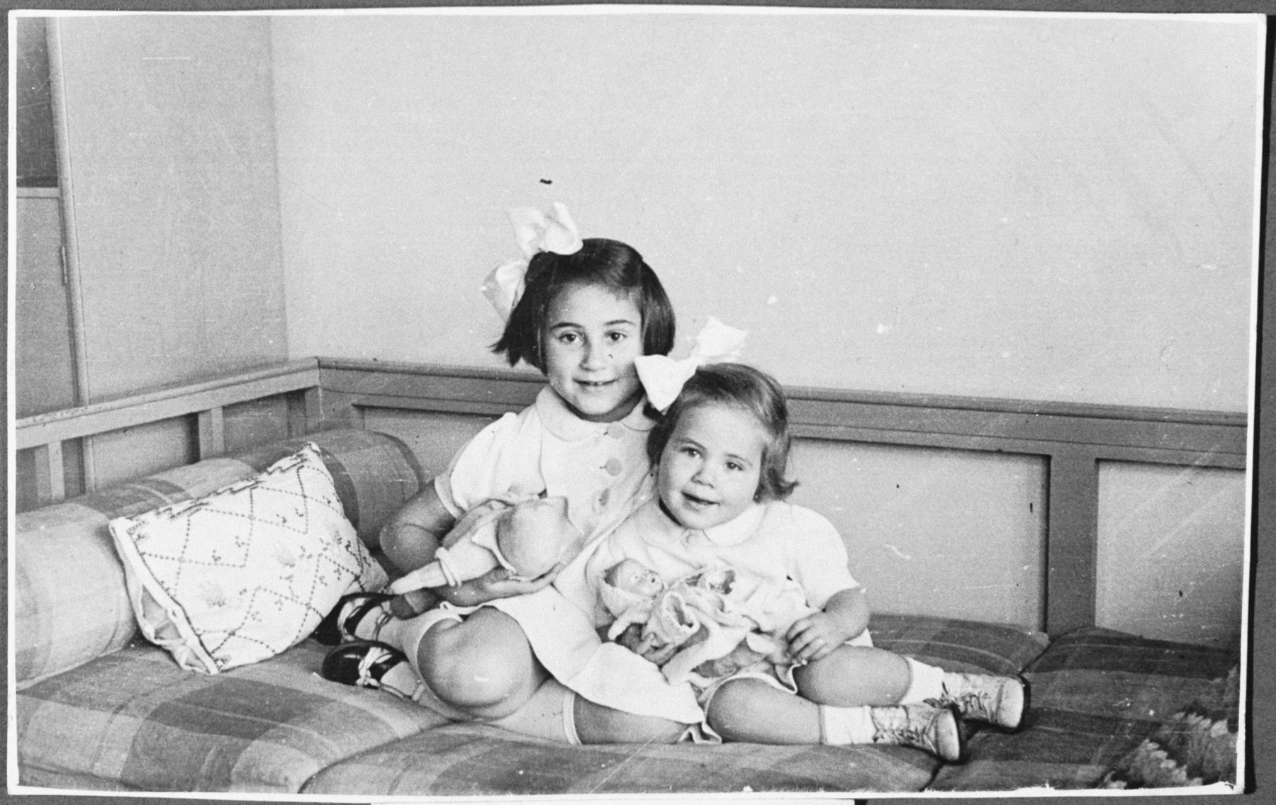 Two sisters pose for a photograph holding their dolls.   Pictured is the donor with her younger sister Karmella (Karmi).