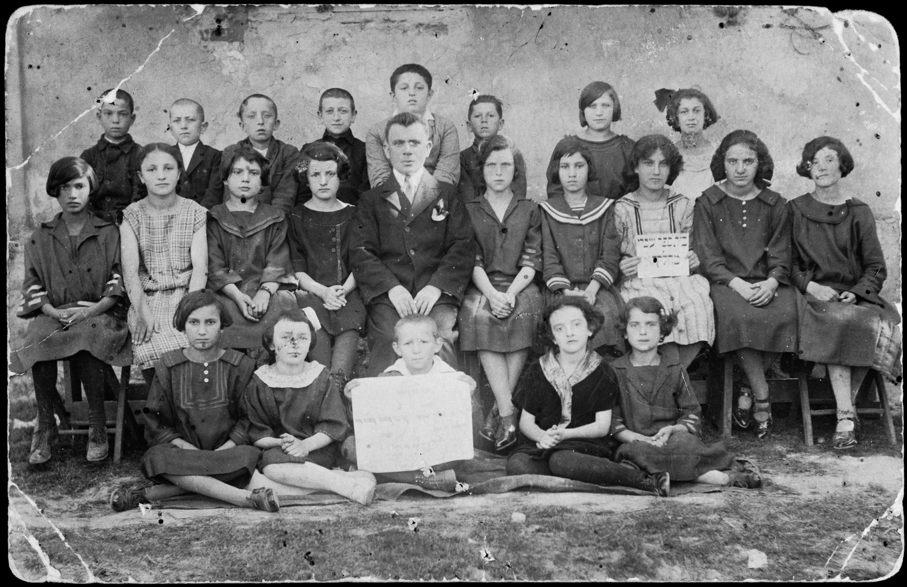 Group portrait of children and faculty in a Hebrew school in Grzymalow.  Lea Somerstein is pictured on the bottom right.