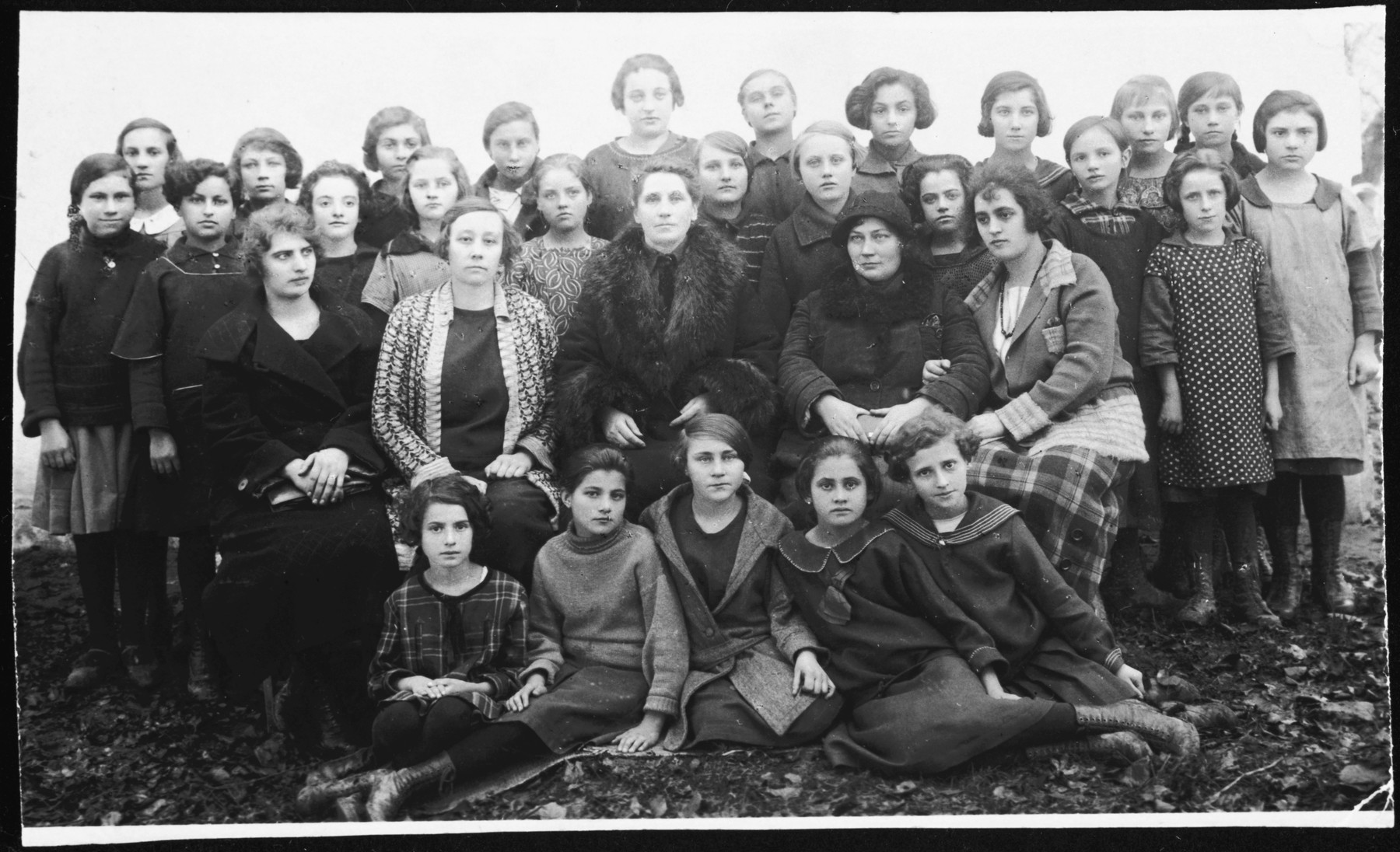 Group portrait of girls and faculty in a Polish school in Grzymalow.  Lea Somerstein is pictured on the bottom right.  The second girl from the left in the upper row is Ernestina (Tina) Hellreich.