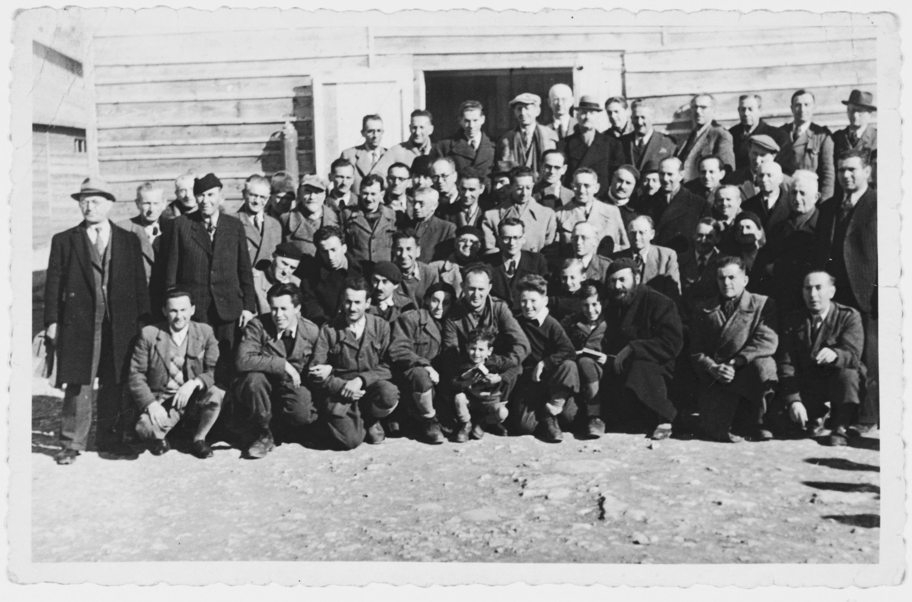 Group portrait of male and child prisoners standing outside their barrack in the Kraljevica concentration camp.  Zlatko Weinrebe is standing on the top row on the far left.