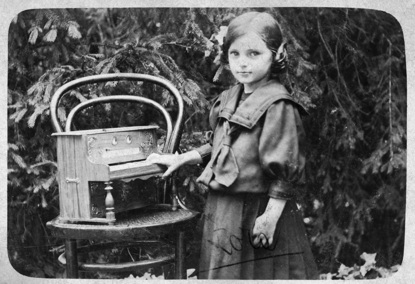 Close-up portrait of a young Jewish girl with a toy piano in a small village outside of Zagreb.  Pictured is Zora Benedik, the mother of the donor.
