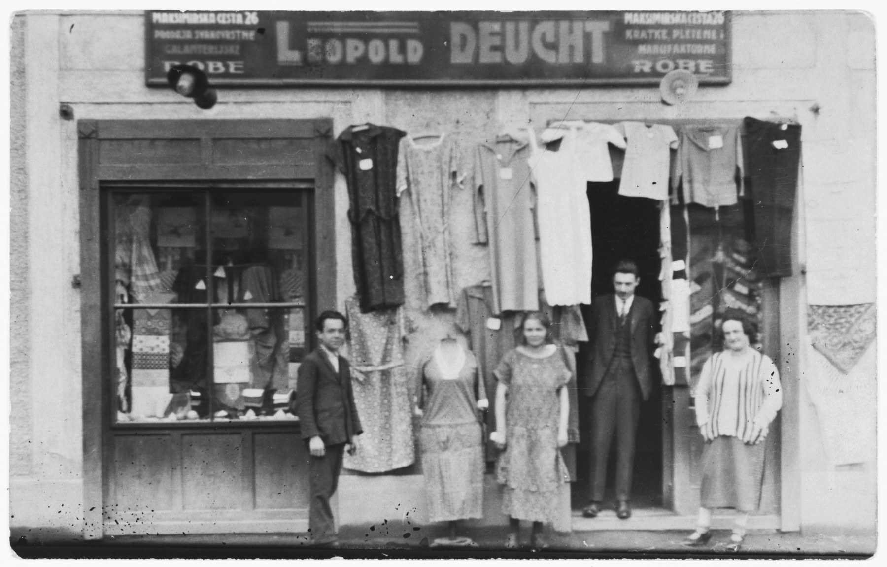 Four people stand outside Leopold Deucht's clothing store.  [The donor does not know who is in the photo but suspects they are related to her uncle Joseph Deucht who perished.]